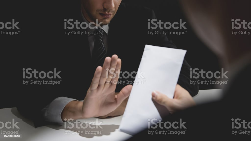 Businessman rejecting money in white envelope stock photo
