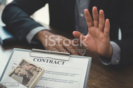 848170878istockphoto Businessman rejecting money that come with  contract 1140471732