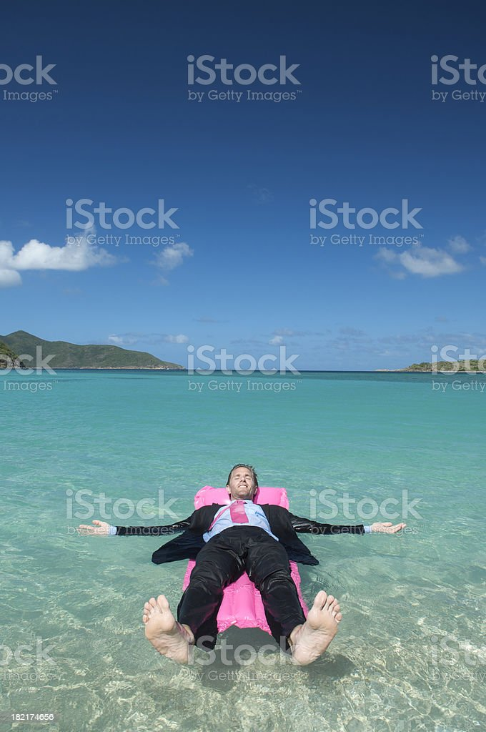 Businessman Relaxes Outdoors in Suit Floating on Pink Air Mattress royalty-free stock photo