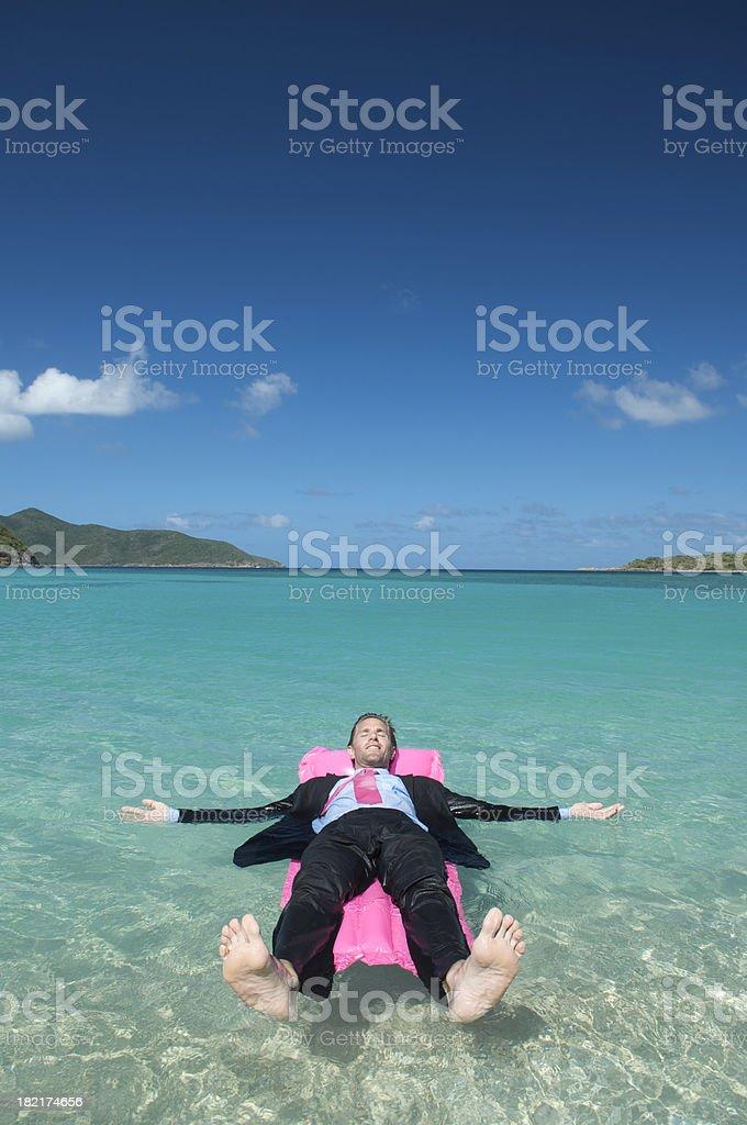 Hombre descansa al aire libre en traje rosa flotando en colchón de aire - foto de stock