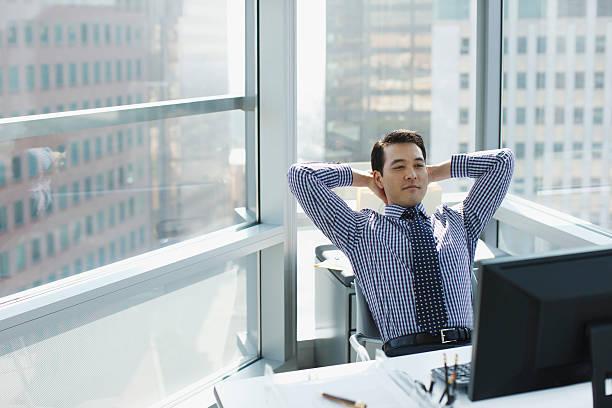 uomo d'affari rilassante alla scrivania in ufficio - mani dietro la testa foto e immagini stock