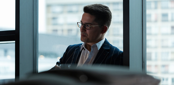 530281733 istock photo Businessman relaxing by the window in hotel room 1193748813