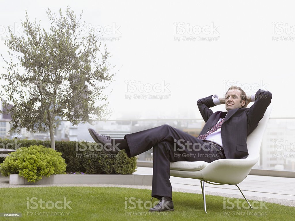 Businessman relaxing in chair outdoors royalty-free stock photo