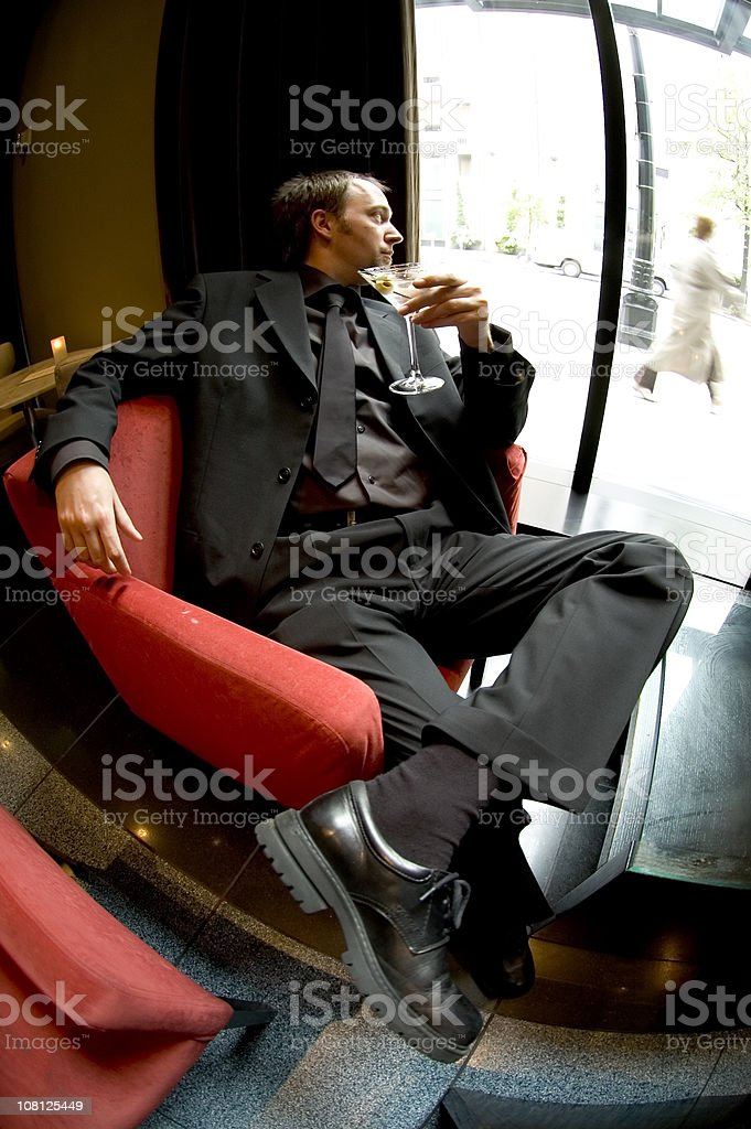 Businessman Relaxing in Chair with Martini, Fish-eye royalty-free stock photo