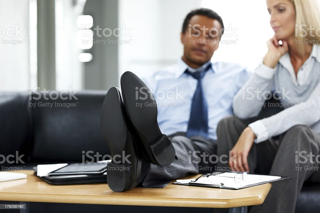 Businessman relaxing in the office with colleague sitting by royalty-free stock photo