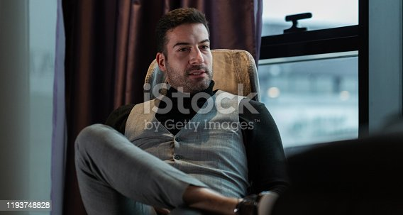530281733istockphoto Businessman relaxing on chair in hotel room 1193748828
