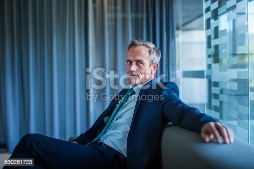 istock Businessman relaxing on sofa in office lobby 530281723