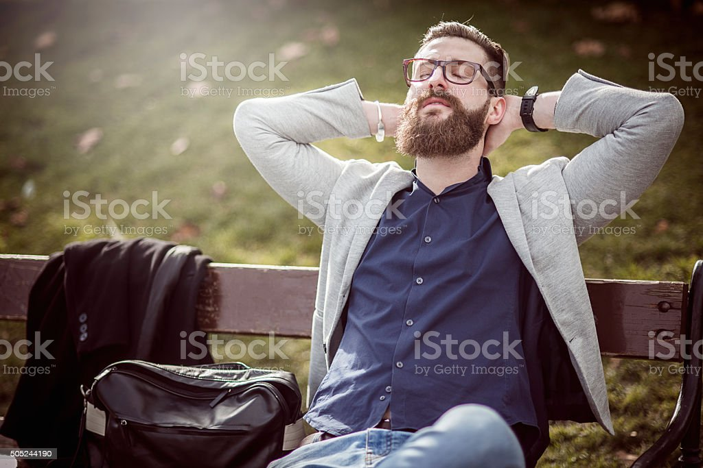 businessman relaxing on the bench after work stock photo