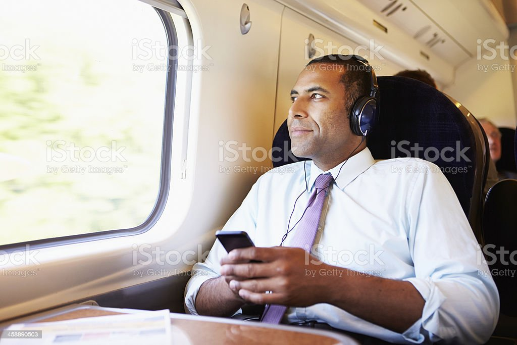 Businessman Relaxing On Train Listening To Music stock photo