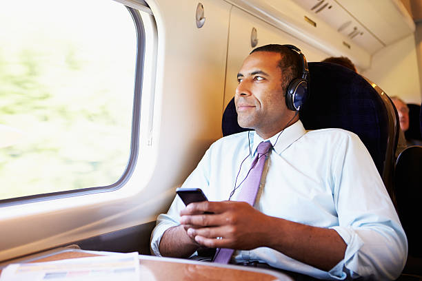 Businessman Relaxing On Train Listening To Music Businessman Relaxing On Train Listening To Music with headphones on mp3 player stock pictures, royalty-free photos & images