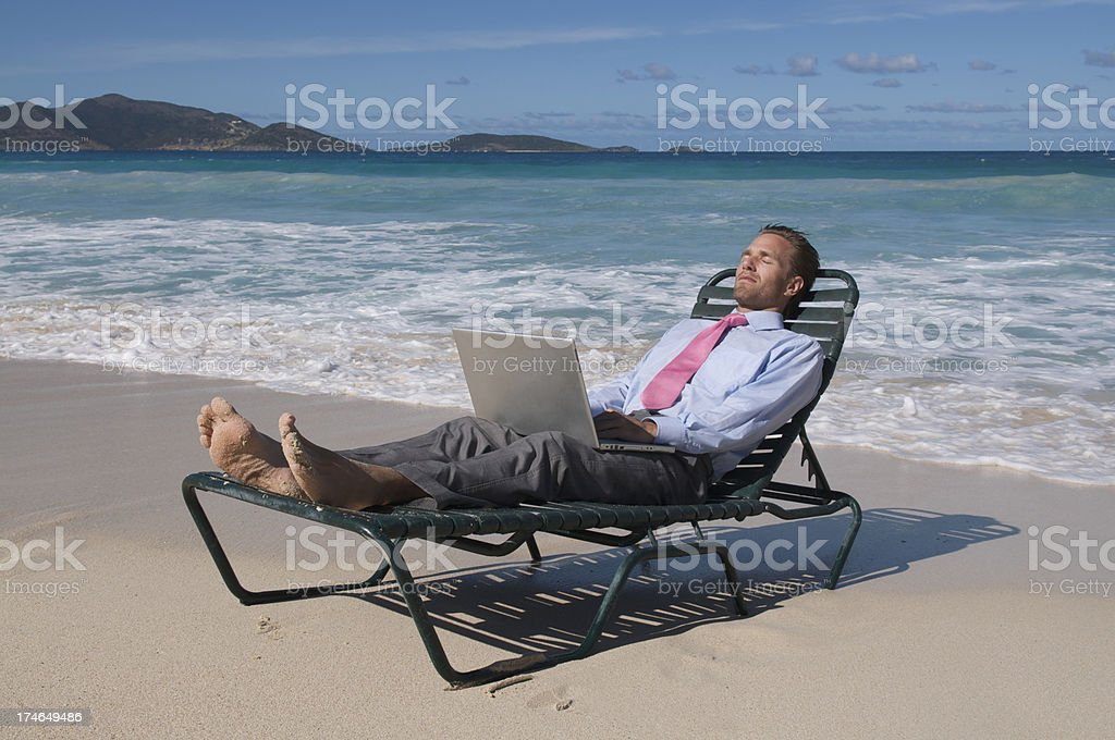 Businessman Relaxing on Tropical Beach in Chair with Laptop stock photo
