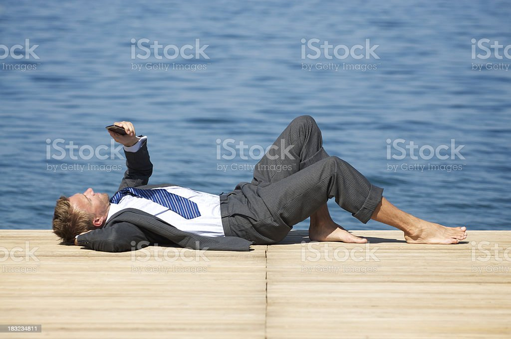 Businessman Relaxing Outdoors on Calm Dock with Smart Phone stock photo