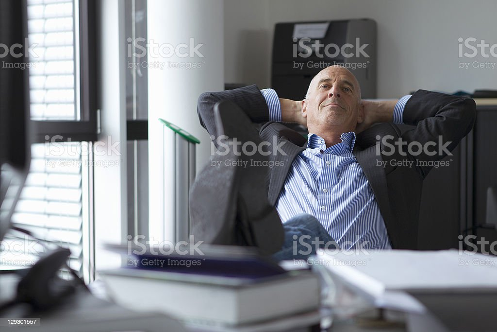 Businessman relaxing with feet on desk stock photo