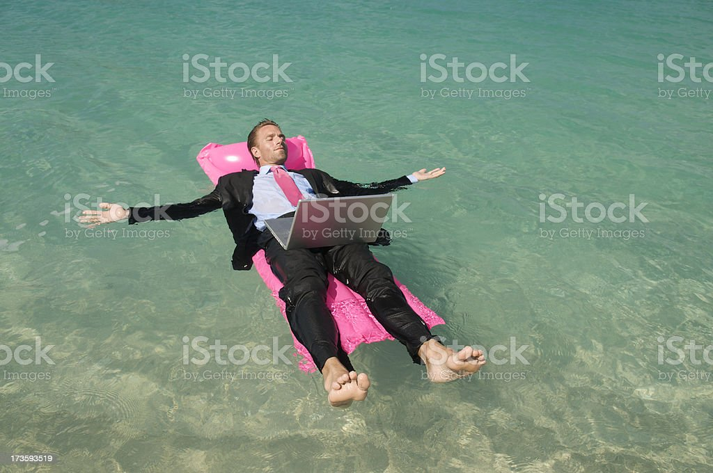 Businessman Relaxing with Laptop Floating on Tropical Sea royalty-free stock photo