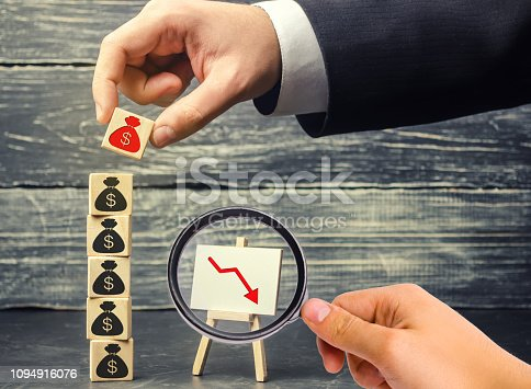istock businessman removes a cube with a picture of dollars. financial and economic crisis. capital outflow. sabotage of the economy. bankruptcy. pressure on small businesses. falling prices. cash loss 1094916076