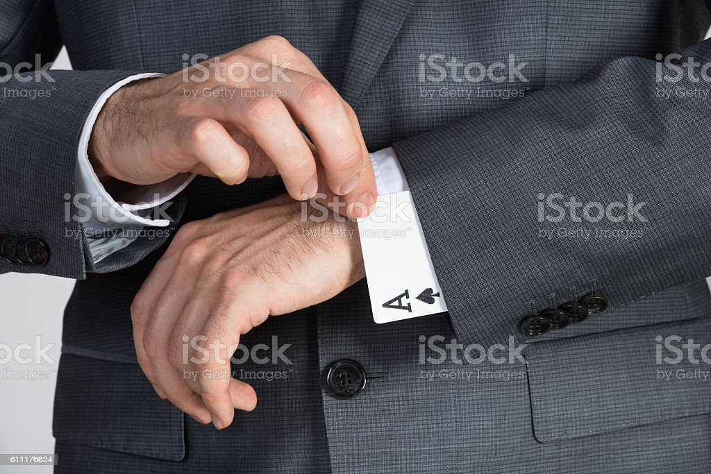 Businessman Removing Ace Cards From Sleeve stock photo