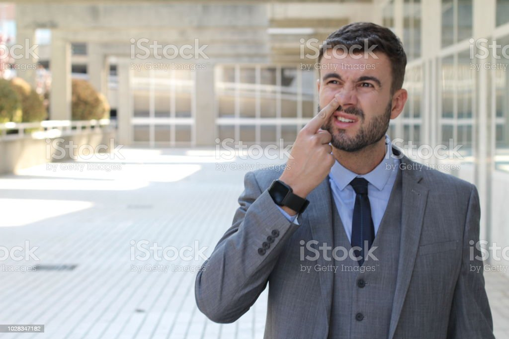 Businessman removing dried nasal secretions stock photo