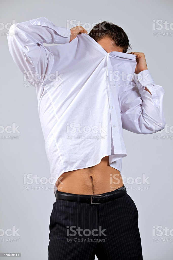Businessman removing shirt at office stock photo