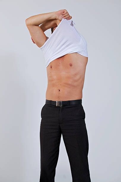 Businessman removing shirt at office Businessman removing shirt at office undressing stock pictures, royalty-free photos & images