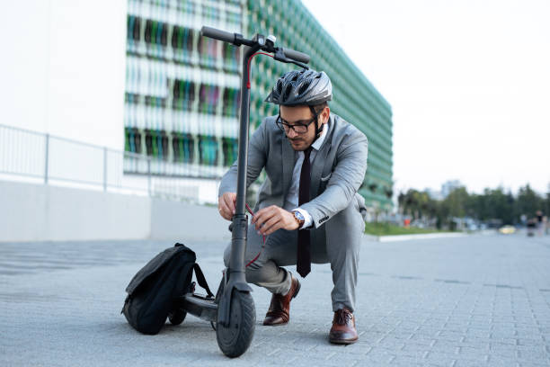 Businessman repairing electric push scooter stock photo