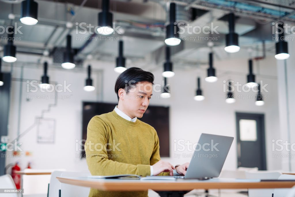 Businessman replying on e-mails in coworking hub in Taiwan stock photo