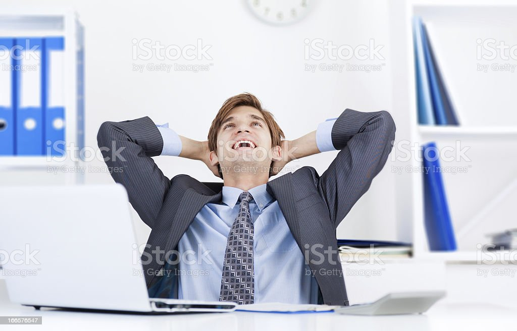 Businessman resting with hands on back of head at work royalty-free stock photo