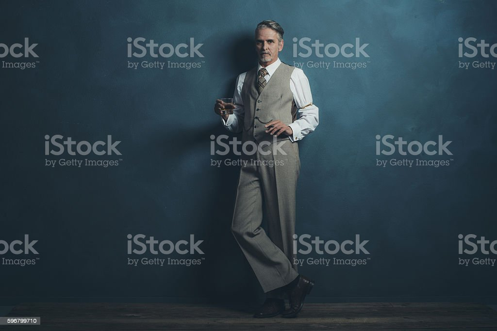 Businessman retro 1920s style holding glass of whiskey and cigar. stock photo