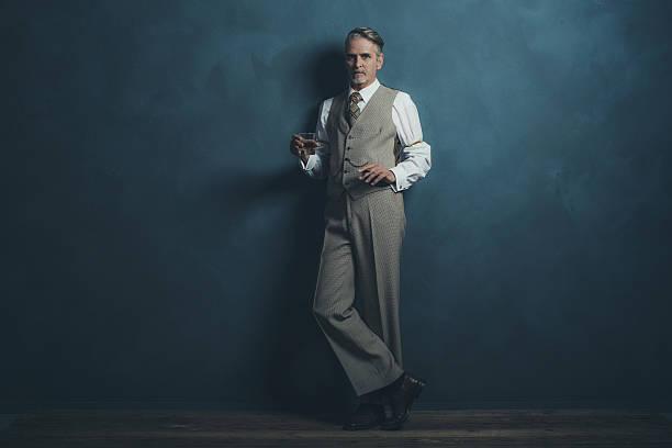 businessman retro 1920s style holding glass of whiskey and cigar. - 20er jahre stock-fotos und bilder