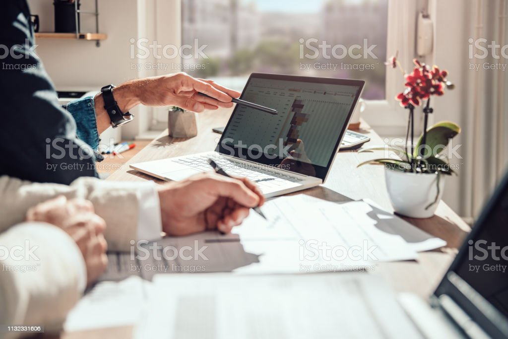 Businessman reviewing project timeline Businessman sitting by the desk and analyzing project timeline Adult Stock Photo