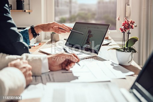Businessman sitting by the desk and analyzing project timeline