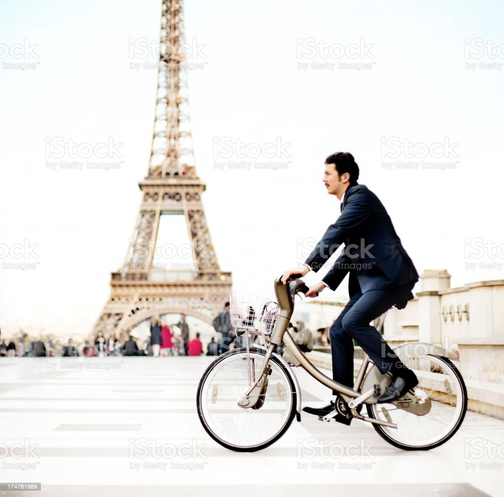 Businessman riding a bike in Paris royalty-free stock photo