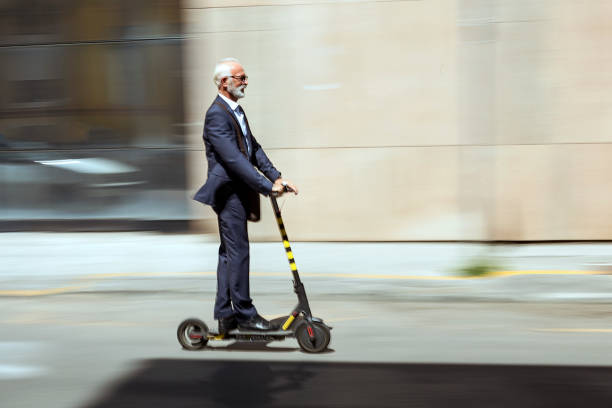 businessman riding a electric scooter in the city - electric push scooter stock photos and pictures