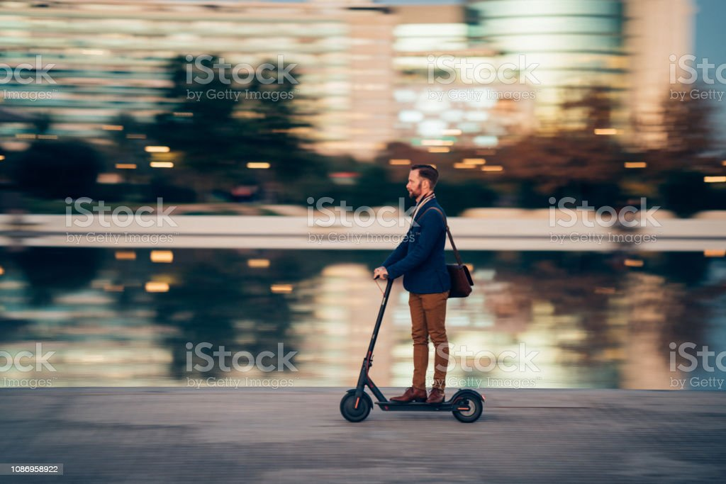 Businessman riding a scooter in the city stock photo