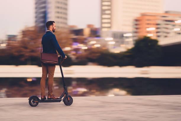 businessman riding a scooter in the city - monopattino elettrico foto e immagini stock