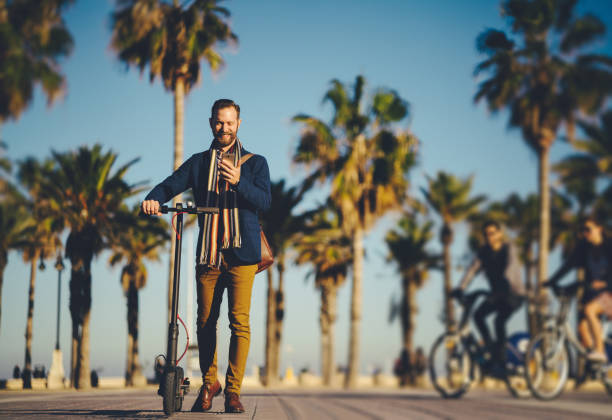 businessman riding an electric push scooter in spain - electric push scooter stock photos and pictures