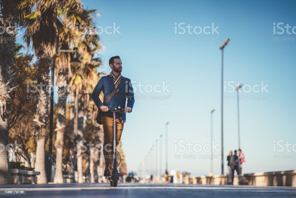 Businessman riding an electric push scooter on his way to work stock photo