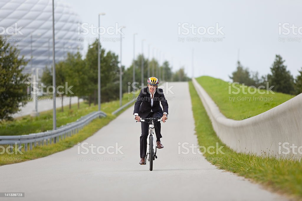 Businessman riding bicycle in urban park stock photo
