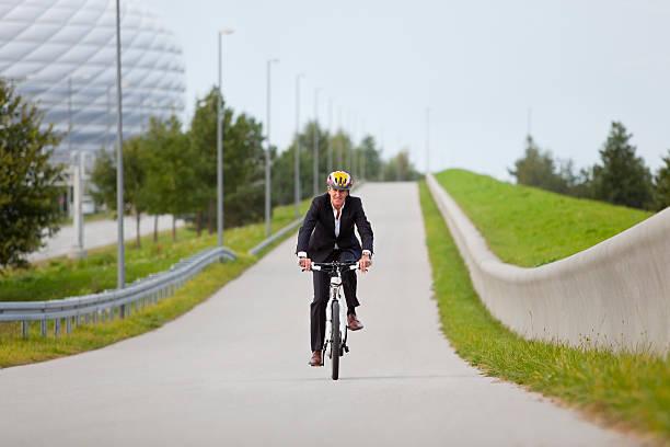 geschäftsmann reiten fahrrad im stadtpark - arbeit in münchen stock-fotos und bilder