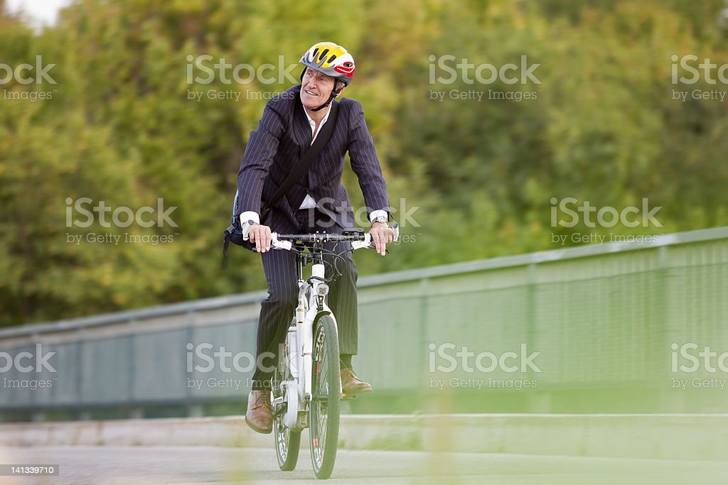 Businessman riding bicycle on bridge stock photo
