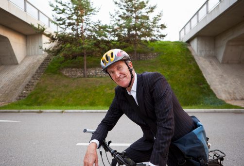 Businessman riding bicycle on street
