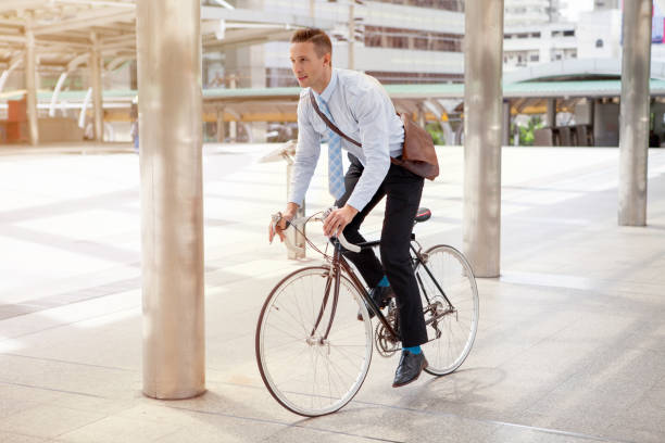 Businessman riding bicycle to work on urban street in morning .transport and healthy stock photo