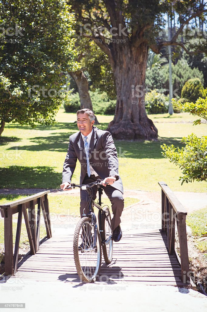 Businessman riding bike in the park stock photo