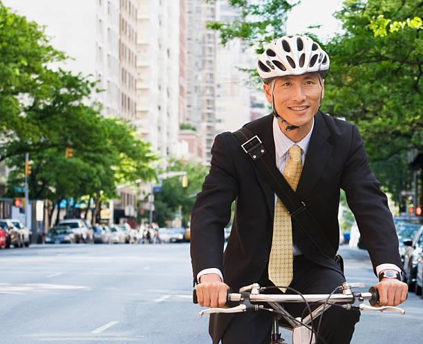 Businessman riding bike stock photo