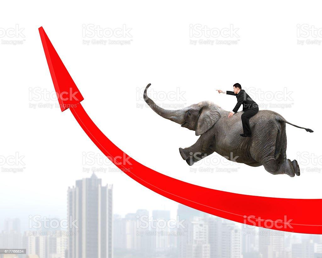 Businessman riding elephant on red arrow up trend line stock photo