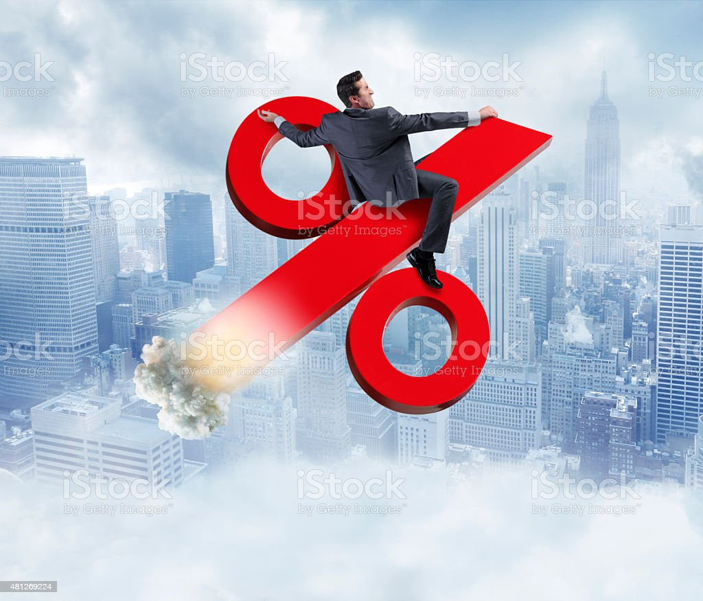 Businessman Riding Rising Percentage Sign stock photo