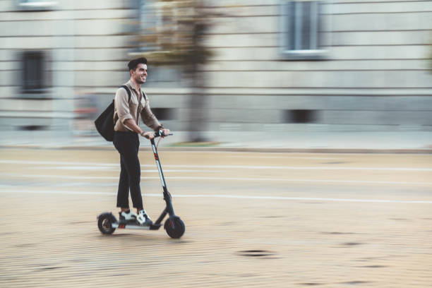 Businessman riding scooter in the city stock photo