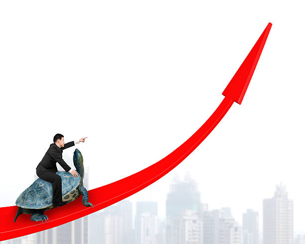 Businessman riding turtle on red arrow up stock photo