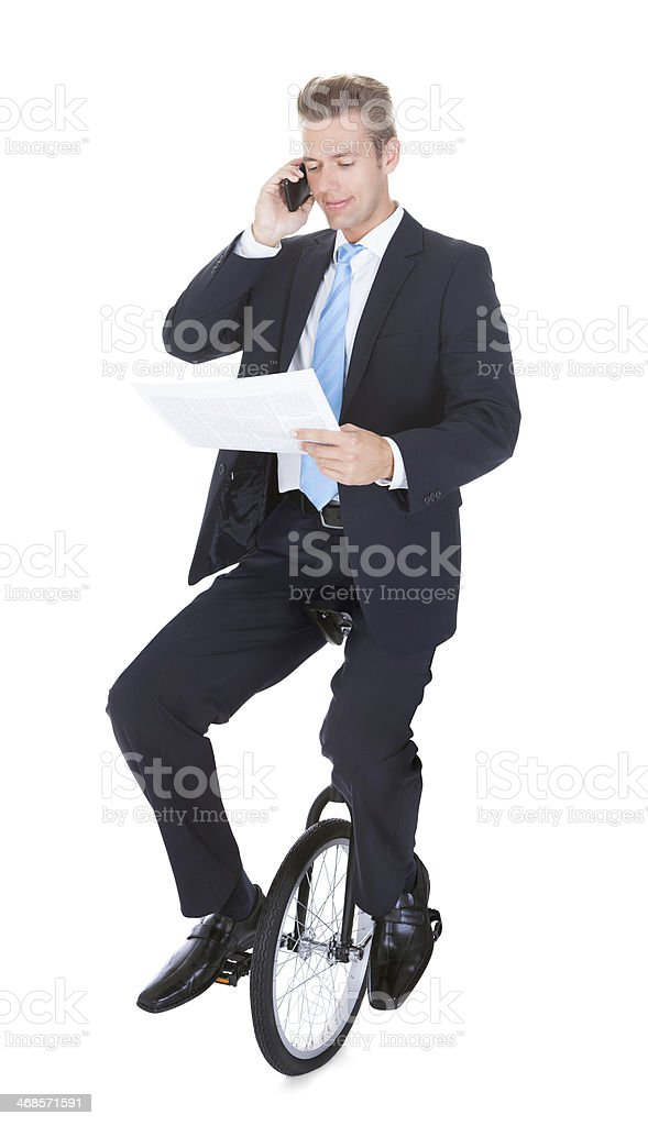 Businessman Riding Unicycle Talking On Cellphone stock photo
