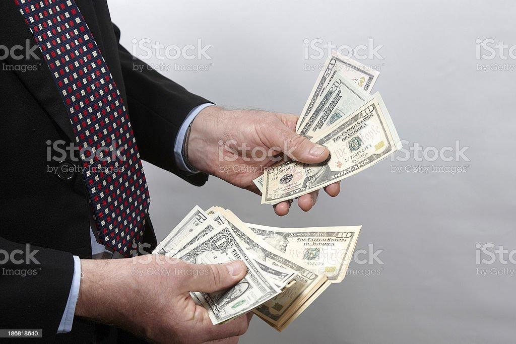 Businessman riffling a wad of dollar bills stock photo