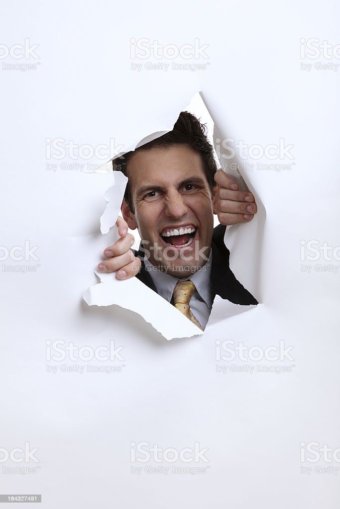 Businessman Ripping Through Paper stock photo